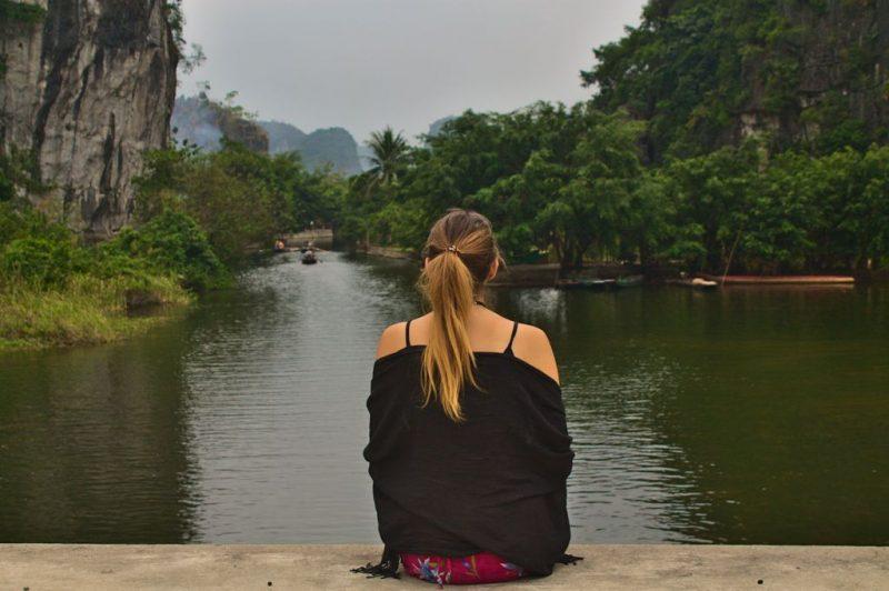 Tina sitting by river, Tam Coc, Ninh Binh, Vietnam