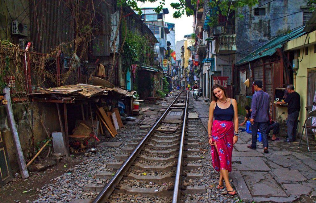 Tina at Hanoi's Train Street walking on railroad track, Vietnam