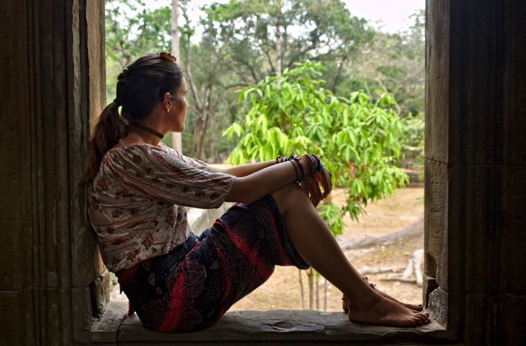 Sitting in the window frame of a temple in Angkor Wat, Siem Reap