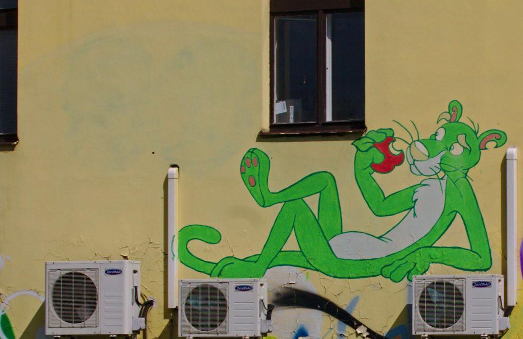 The Pink Panther, but green, eating an apple (streetart Bubeneč)