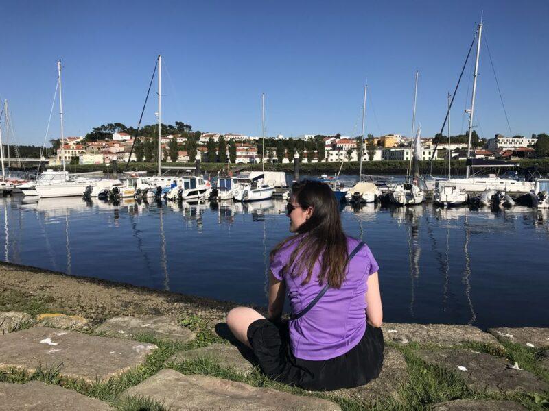 Andrea sitting at harbor, Camino Portugues