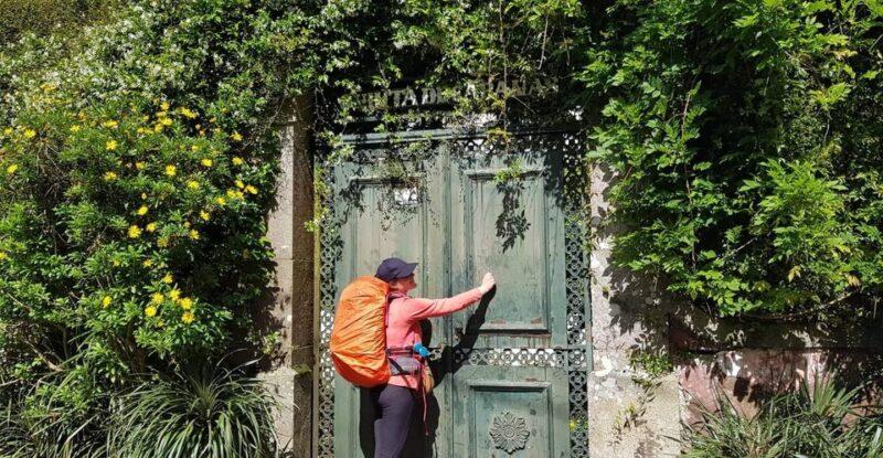 Tina knocking on overgrown gate, Camino Portugues, Portugal