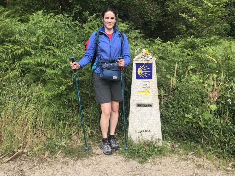 Andrea at a camino signpost, yellow arrow, Camino Portuges