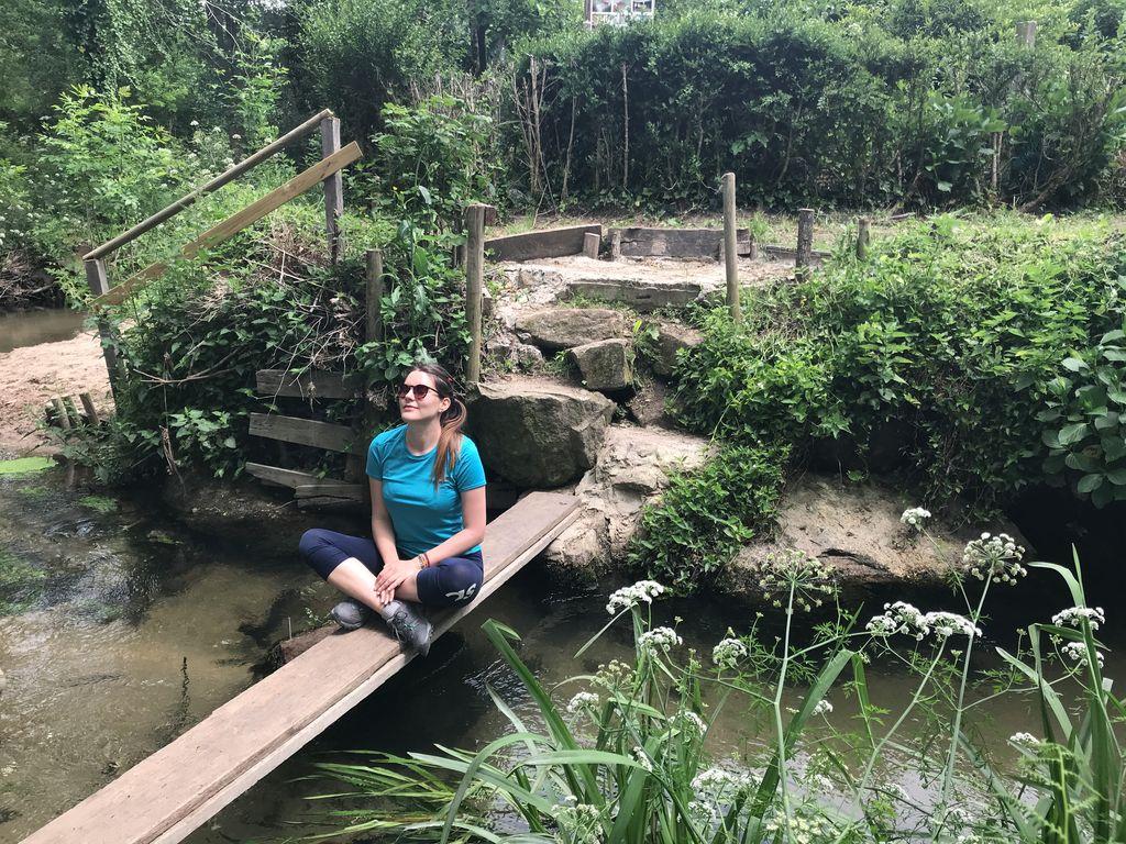 Tina sitting by river, Camino Portugues
